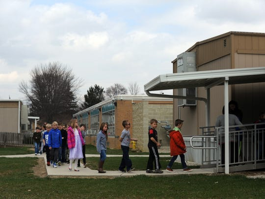 Bloom-Carroll Primary second graders walk from their classroom in a trailer, left, into a trailer that houses music and art classes, right. All of the school's six second grade classes are in a set of a trailers next to the school's main building.