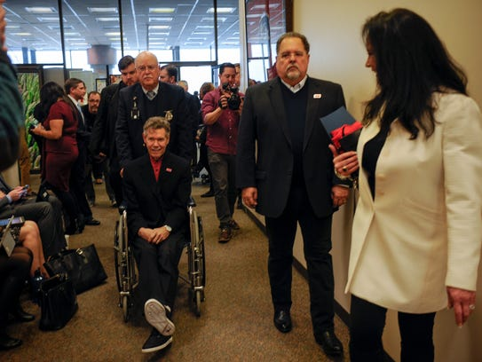 Randy Travis takes a wheelchair to a committee room