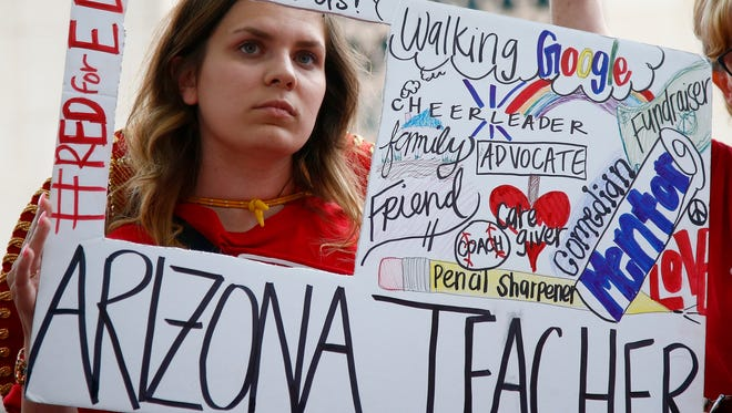 Teacher Taylor Dutro listens as protest organizers announce Arizona teachers intentions to go back to work if lawmakers pass a school funding plan, during the fourth day of the statewide teachers' strike at the Arizona Capitol on  May 1, 2018, in Phoenix.