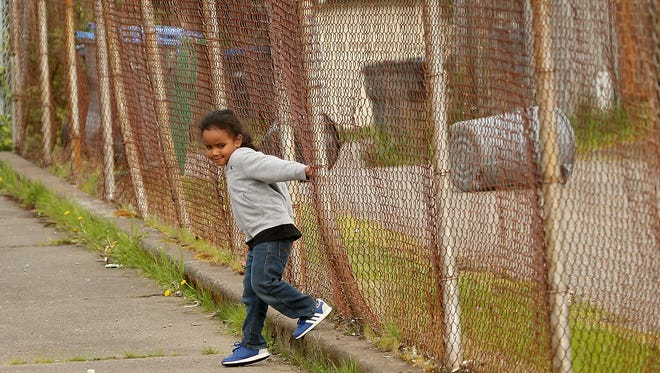 Deion Littleraven-Oliver, 4, holds on to the rusty fence at the Warren Avenue Playfield on Tuesday while his brother played baseball. Bremerton parks officials are in the early stages of a revamp of the aging playfield.