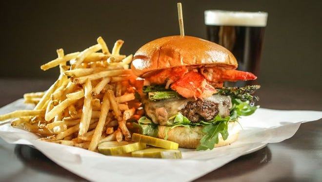 The Surf and Turf grilled burger, $14.95, at Yard House is topped with lobster, grilled asparagus, arugula, swiss and tomato bearnaise.