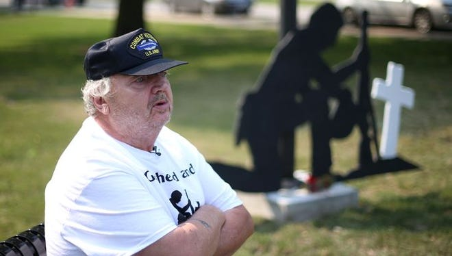 Al Larsen, an Army veteran who served during Vietnam, becomes emotional as he shares his story of a friend who was killed in Vietnam. Larsen, who sculpted a wooden marker of a soldier kneeling at a grave, is among many upset in Knoxville that the marker is under scrutiny due to the cross, a religious symbol, being located on city property. Larsen said the cross isn't intended to be a religious statement, rather a symbol of a soldier's gravesite.