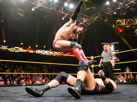 WWE's NXT champion Finn Balor stomps on an opponent  during a wrestling event in Winter Park, Florida.
