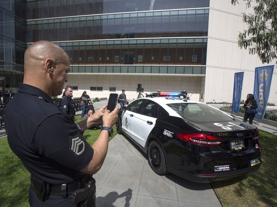 A Los Angeles police officer photographs a hybrid car at the unveiling of two new Ford Fusion hybrid pursuit-rated Police Responder cars at LAPD headquarters on April 10, 2017. The LAPD is committed to purchasing at least 300 hybrid and hybrid-electric plug-in vehicles by 2020.