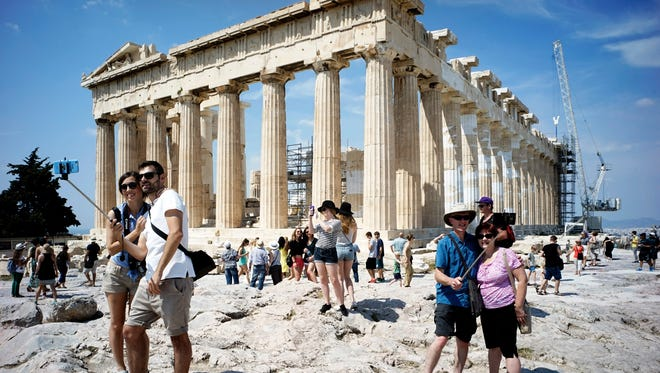 Tourists visit the ancient Acropolis hill, with the ruins of the 5 B.C. Parthenon temple on June 30, 2015 in Athens, Greece.
