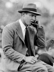 FILE - In this Nov. 1949 file photo, Oklahoma coach Bud Wilkinson talks on the sideline on a phone during a college football game in Norman, Okla. By the 1950s, college football's balance of power had drifted away from the elite eastern schools and into the Midwest, where Wilkinson's Oklahoma dynasty dominated the polls and set a record winning streak that still stands. (AP Photo/File)