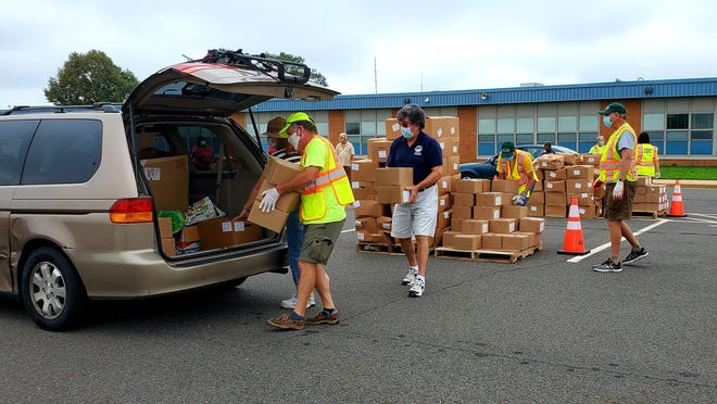 Volunteers help pack up a car with food boxes during Burlington County's distribution event on Tuesday.