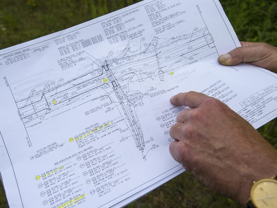 Joseph Depaolis of Boswell Engineering holds plans showing an underpass to link two recreation paths that is to be built under U.S. 7 in Charlotte.