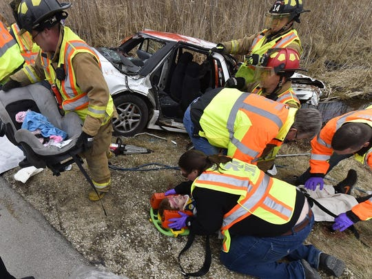 Algoma High School student Tyler Paplham is worked on by Kewaunee County fire and rescue during a program re-enacting a two-vehicle drunk driving accident Wednesday at Algoma High School. Paplham played one of the drivers injured in the crash.