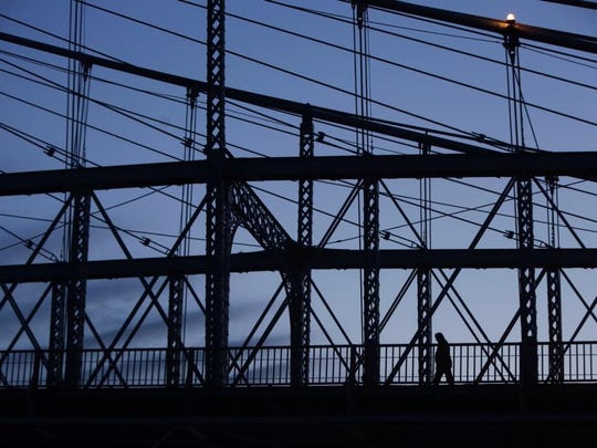 A pedestrian crosses Roebling Suspension Bridge as the sun begins to rise on Monday morning.