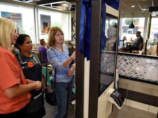 Jacqueline Binkley, center, uses the new self-serve