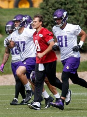 Vikings quarterback Kirk Cousins, center, jogs with tight ends Josiah Price, left, and Blake Bell during practice in Eagan, Minn., June 14.