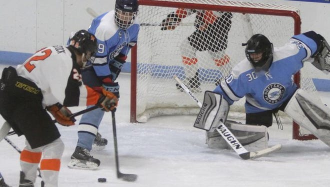Jason Bienstock attempts to score between Troy Daniels and Sean Gordon. Mamaroneck defeated Suffern 4-2 in a varsity hockey game at Hommocks Park Ice Rink in Larchmont Jan. 29, 2016.