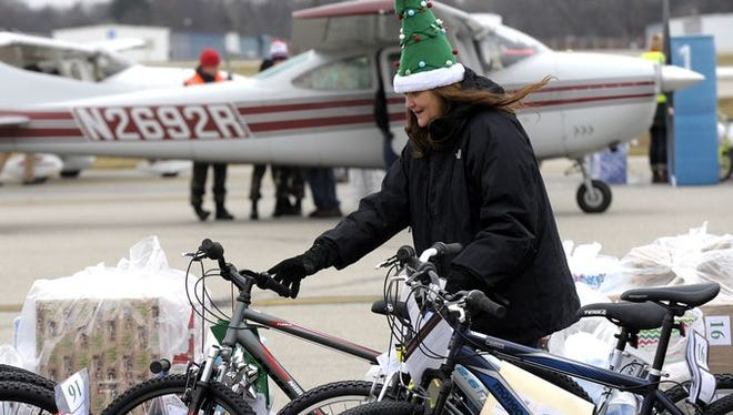 Volunteer Cindy Romeos, 58, of Waterford, prepares to help load these bicycles onto planes for delivery. She volunteers in the memory of her son, Christopher Dean Katranis, who died nine years ago at age 21.