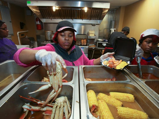 Nichelle Thurston prepares an order of crab legs at The Seafood Lady restaurant at Seventh and Oak streets.  Her husband, Luke Thurston, owns the Old Louisville business which has been growing in popularity.