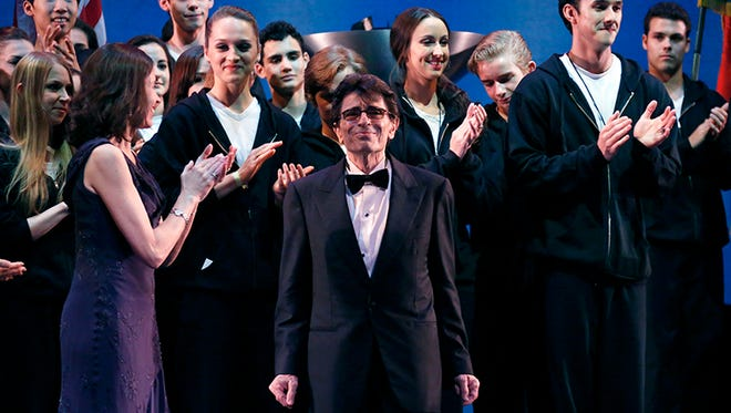 Dancers, instructors and judges applaud as Edward Villella, center, chairman of the 2014 USA International Ballet Competition takes the stage during the  opening ceremony in Jackson, Miss., Saturday, June 14, 2014.