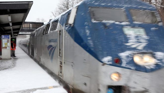 A Metro-North maintenance worker pauses his snow shoveling while an Amtrak train rushes past the Cold Spring station on Feb. 5, 2014.