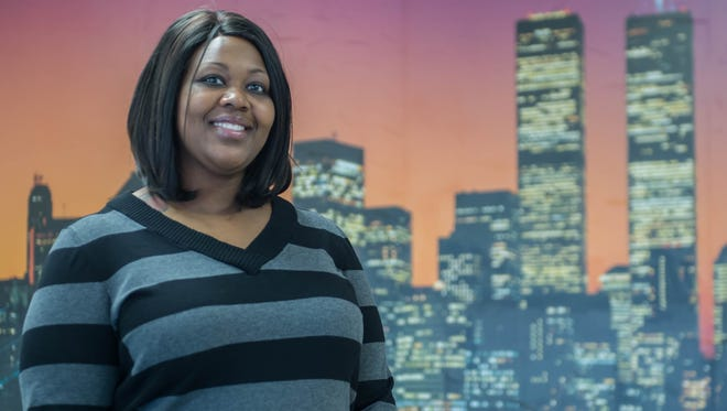 Kirby Thornton, owner of New York Grill, stands in front of a mural of the New York City skyline at her restaurant.