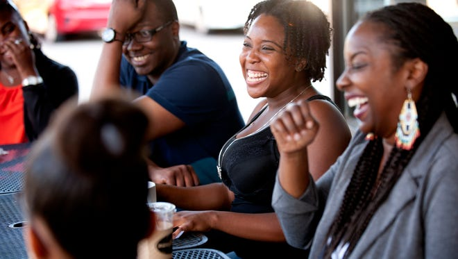 From left to right, Alounso Gilzene, Courtney Gibbons and Danielle Culberson laugh during a Coffee & Chill gathering of the Black Market on Wednesday, Aug. 31, 2016 at Chapelure in East Lansing. The Black Market is an organization which works to bring together young professionals.