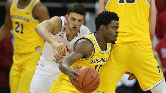 Wisconsin guard Zak Showalter chases Michigan guard Derrick Walton Jr. during U-M's 68-64 loss to Wisconsin on Tuesday, Jan. 17, 2017 in Madison, Wis.