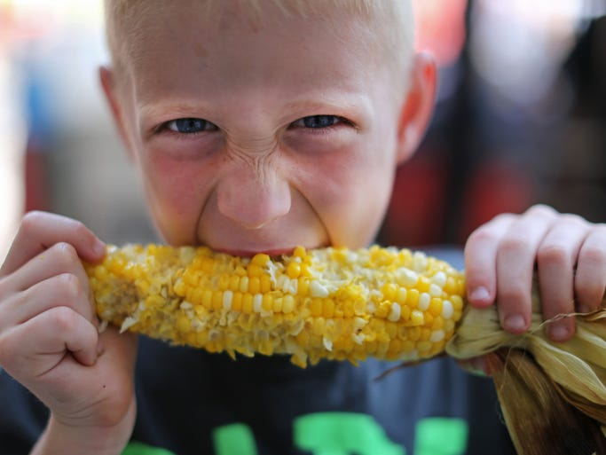 Keagan Leisure, 8, of Mason, enjoys an ear of fresh corn from Pit to Plate at Taste of Cincinnati Saturday. The three day event along 5th street downtown includes food, drinks, entertainment, rides and other games for kids and much more. Thousands are expected to attend.
