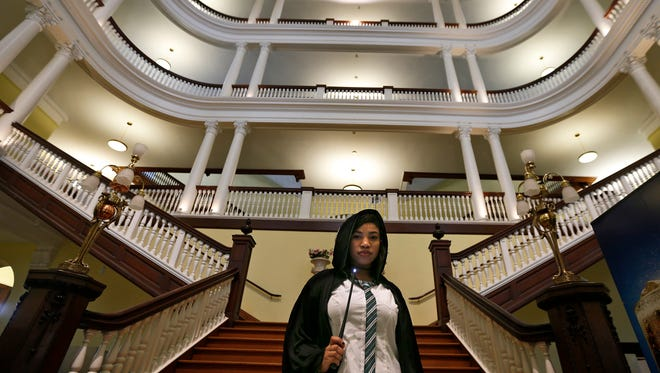 In this Oct. 22, 2016, photo, Celess Leblanc, from the New York City borough of Queens, dresses in costume while attending an annual festival in Philadelphia based on the Harry Potter fantasy series conceived by British author J.K. Rowling, and holds a wand while posing for a photograph inside Chestnut Hill College's St. Joseph Hall in the Chestnut Hill neighborhood of Philadelphia. In 2018, Warner Bros. notified organizers of Harry Potter fan festivals around the U.S. of new guidelines prohibiting any use of names, places or objects from the fantasy series, in an effort to crack down on unauthorized commercial activity at such events. (David Maialetti/The Philadelphia Inquirer via AP)