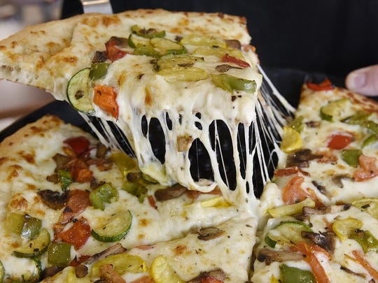A pizza at Sliced in St. Joseph is served, complete with a glorious cheese pull.