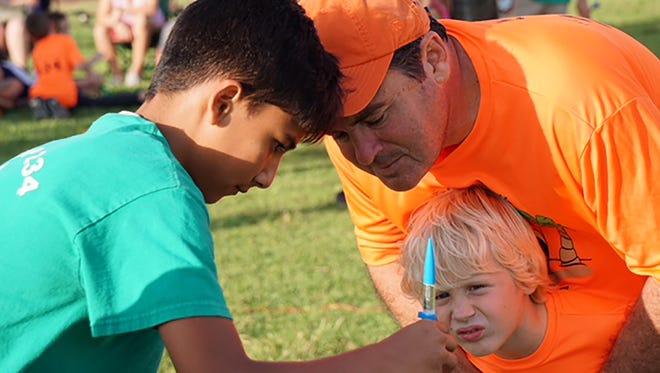 Boy Scout Alejo Ruiz-Vallejo assists Ed Kelly and his son Cub Scout Edward Kelly.
