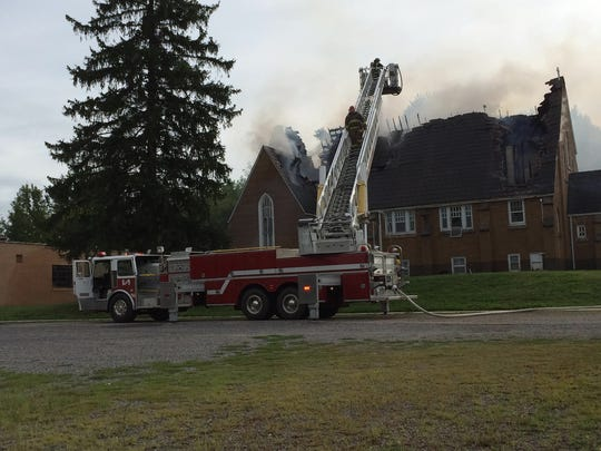 Firefighters work to extinguish a fire at the Rudolph Moravian Church in August.