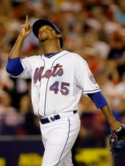 Mets pitcher Pedro Martinez points skyward as he leaves