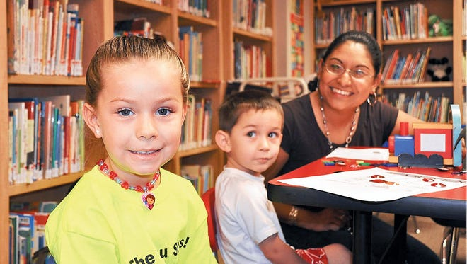 Sonia Moreno shares time with Myranda and Mason Weatherford at the Marshall Memorial Library as part of the Children's Reading Foundation of  Luna County. Moreno is the program's executive director.