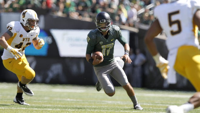 The Duck's Jeff Lockie runs the ball in the fourth quarter of their game with the Cowboys on Saturday, Sept. 13, 2014, in Eugene, Ore.