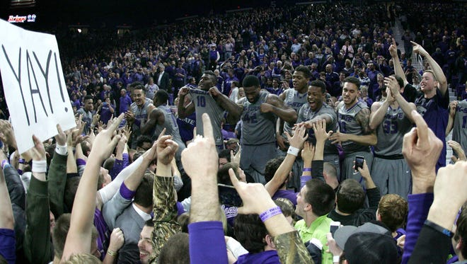 Kansas State Wildcats players celebrate on the scorers table following a 70-63 win against the Kansas Jayhawks