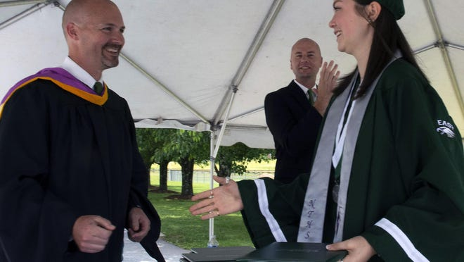 Morgan Carpenter became the first official member of the class of 2020 at East Henderson High to get her diploma from Principal Carl Taylor during a drive-through commencement held Friday at the school. About 200 other seniors received their diplomas within the next several hours.
