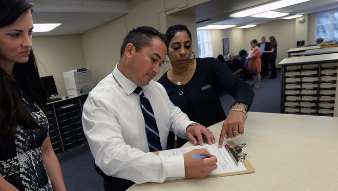 Mario Cahvez goes over his paperwork with clerk Monique Warren as his wife Katy stands by while qualifying to run for Caddo Commission Dist. 10.