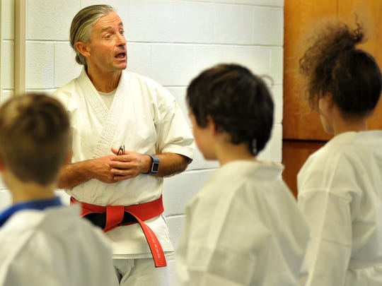 Kirby Middle School physical education and martial arts instructor Ray Silverstrand talks with his class shortly before beginning warm-up training.