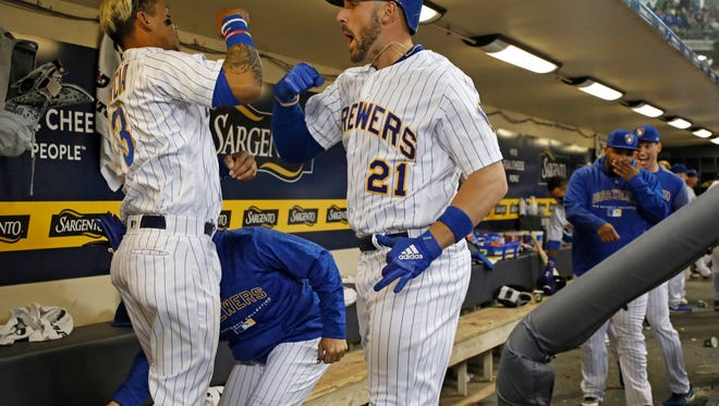 Milwaukee Brewers' Travis Shaw (21) celebrates his two-run home run against Chicago Cubs starting pitcher Kyle Hendricks with teammate Orlando Arcia in the dugout during the fifth inning of a baseball game Friday, April 6, 2018, in Milwaukee. (AP Photo/Jeffrey Phelps) ORG XMIT: WIJP113