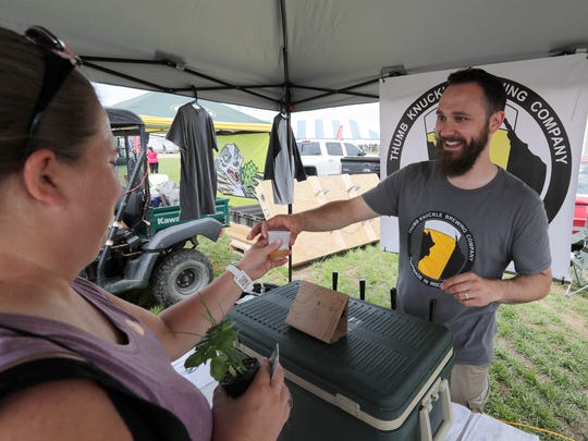 Thumb Knuckle Brewing co-owner Ed Thiry distributes beer samples of Tuesday at the 2017 Wisconsin Farm Technology Days in Algoma.