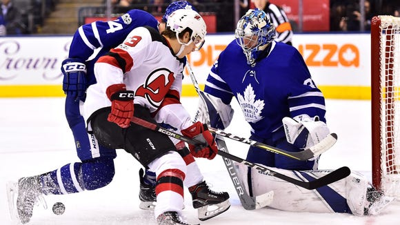 Toronto Maple Leafs goalie Frederik Andersen (31) makes a save on New Jersey Devils center Nico Hischier (13) as Maple Leafs defenseman Morgan Rielly (44) defends during the third period of an NHL hockey game Thursday, Nov. 16, 2017, in Toronto. (Frank Gunn/The Canadian Press via AP)