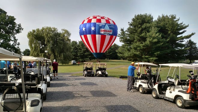 Golfers gather in anticipation of the dramatic hot-air balloon golf ball drop at the Trumansburg Rotary 20th Annual Golf Classic.