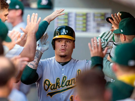 FILE - In this Sept. 2, 2017, file photo, Oakland Athletics' Bruce Maxwell is congratulated by teammates in the dugout after hitting a solo home run off Seattle Mariners starting pitcher Yovani Gallardo during the second inning of a baseball game, in Seattle. Maxwell pleaded guilty Friday, April 14, 2018, to disorderly conduct in an incident in which he was accused of pointing a handgun at the head of a woman who delivered food to his home in Scottsdale, Arizona. Defense attorney Rhonda Neff says Maxwell pleaded to an undesignated felony, meaning the offense will go down to a misdemeanor upon successful completion of his probation.(AP Photo/Stephen Brashear, File)