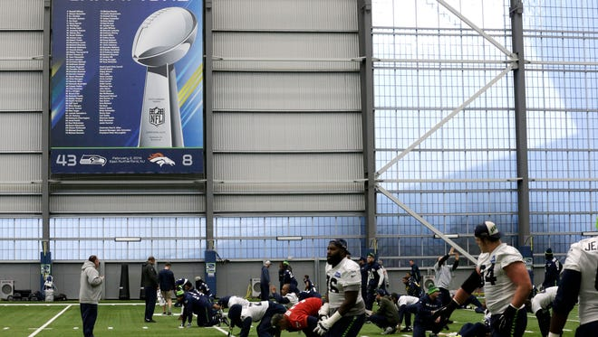 Seattle Seahawks players stretch near a Super Bowl XLVIII banner touting their victory over the Denver Broncos during NFL football practice, Wednesday, Jan. 6, 2016, in Renton, Wash.