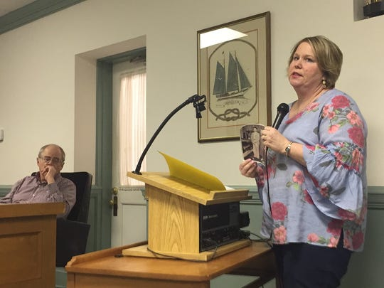 Ruth Chandler Dize, holding a photograph of her parents, speaks during a public hearing at the Onancock Town Council meeting on Monday, March 26, 2018 in Onancock, Virginia.