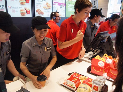 The Vietnamese staff and foreign trainers serve customers during McDonald's opening day in Ho Chi Minh City. The restaurant is the fast-food empire's first in Vietnam.
