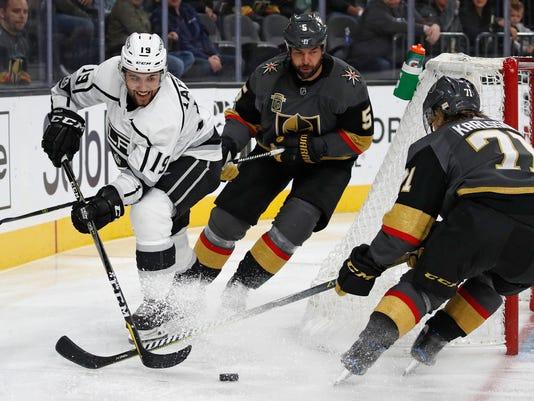 Los Angeles Kings center Alex Iafallo, left, passes around Vegas Golden Knights defenseman Deryk Engelland, center, and center William Karlsson during the third period of an NHL hockey game, Sunday, Nov. 19, 2017, in Las Vegas. (AP Photo/John Locher)