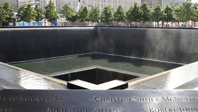 "The ""Reflecting Absence,"" the National 9-11 Memorial in New York City pays tribute to those who died in the terrorist attacks on September 11, 2001. When standing at the edge of the 9-11 Memorial, sheets of water tumble into two shallow pools at the National 9/11 Memorial on Ground Zero in New York City. When visiting the 9-11 Memorial you can read the names of all those that lost their lives that day as you walk around the 9-11 Memorial. Visitors insert flowers into some of those names and an be seen all around the edge of  the 9-11 Memorial."