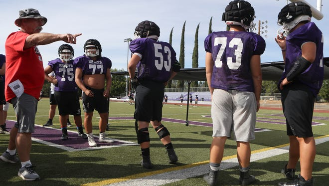 Shasta High School offensive line and defensive line coach Matt Hunsaker works with the offensive line Monday during practice at the school in Redding.