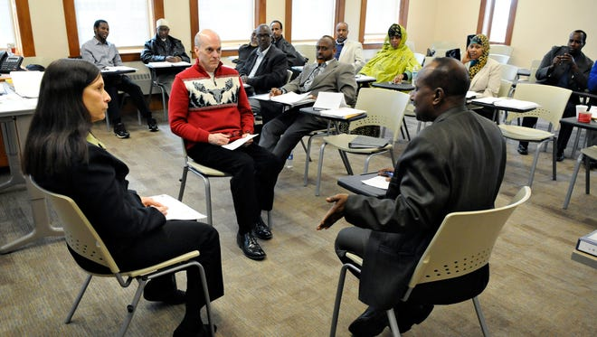 Karmit Bulmar, executive director of the Conflict Resolution Center in Minneapolis, and Jeff Ringer, chair of the Communications Department at St. Cloud State University, do a role-playing exercise with Bashir Budul during a mediator training session at SCSU on March 21.