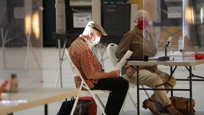 Marshfield poll worker Ned Bangs looks over last minute instructions on Tuesday before the polls opened at 7 a.m.