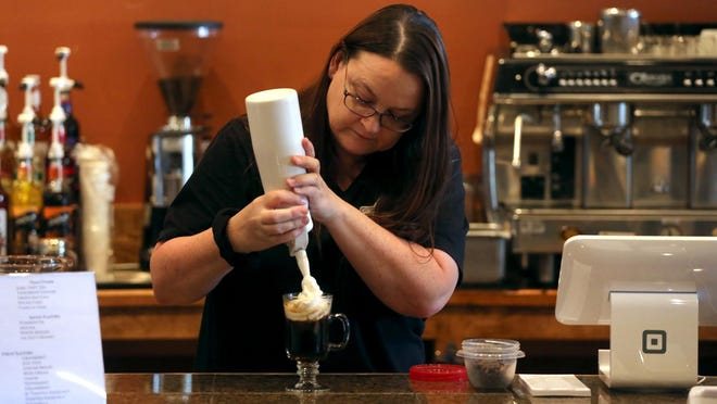Pilar Michelle Huggins adds whipped cream to a drink at Revolution Brewhouse on Monday.